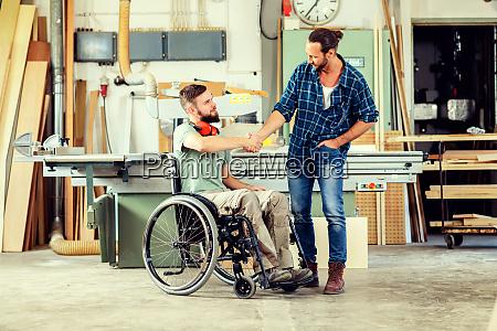 pracownik na wozku inwalidzkim w warsztacie