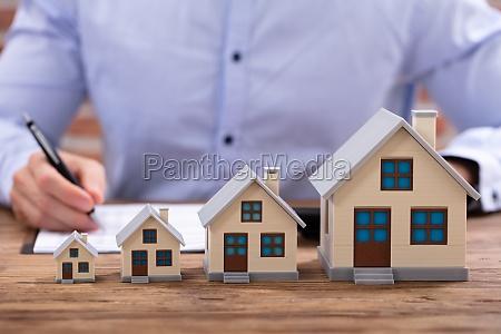 biznesmen obliczanie faktury z modelu domu