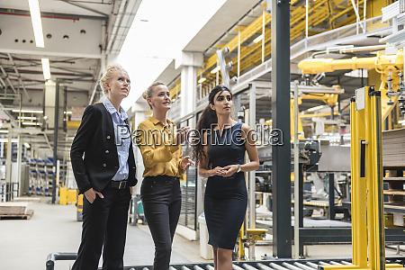 three women talking in modern factory