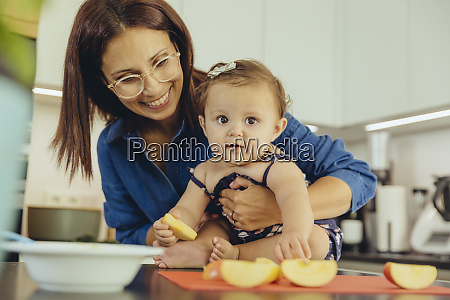mother and baby daughter eating apple