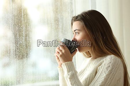 teen picie kawy patrzac przez okno