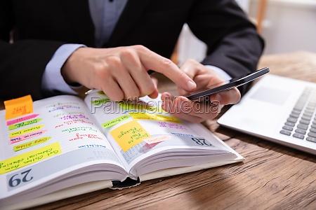 biznesmen holding telefon pisanie harmonogram w