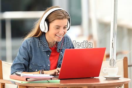 szczesliwy uczen sluchajacy samouczka wideo w