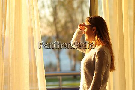 szczesliwy nastolatek zwiadowczy przez okno w
