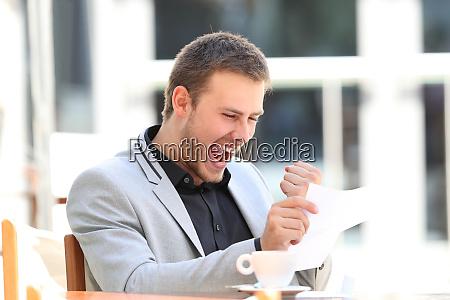 podekscytowany wykonawczy czytania listu w barze
