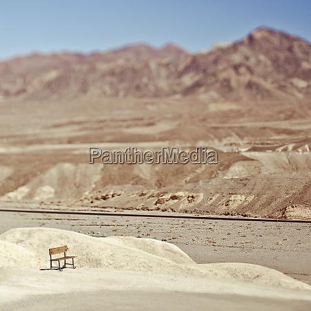 pusta lawka w pustynnym krajobrazie