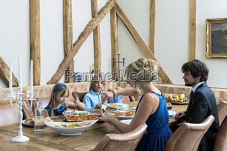 caucasian family eating dinner in dining