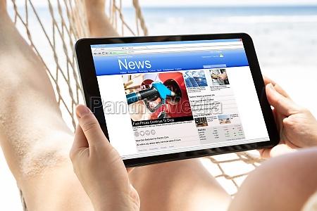 woman watching news on digital tablet