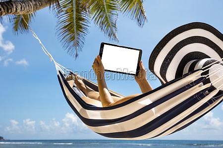woman lying on striped hammock using