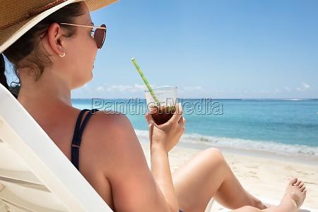 mloda kobieta cieszac sie drinkiem na