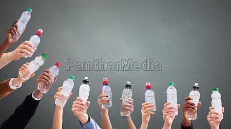 rozne osoby trzymajace butelki z woda