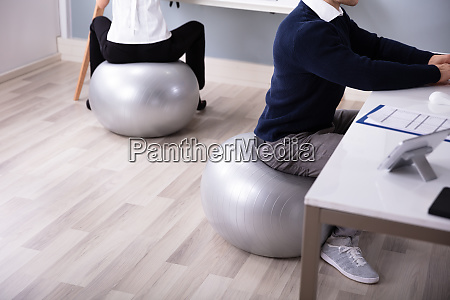 businesspeople working in office sitting on