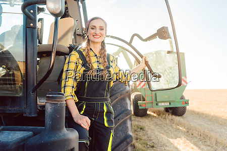 kobieta rolnik stoi przed ciagnikiem na