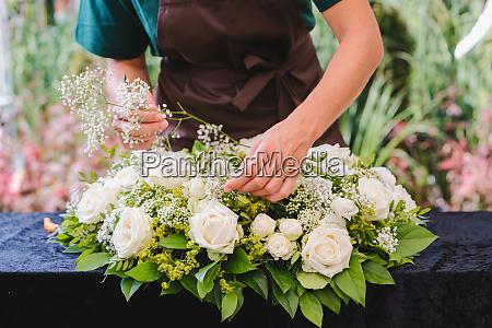 ogrodnik kobieta tworzaca dekoracje grobowa