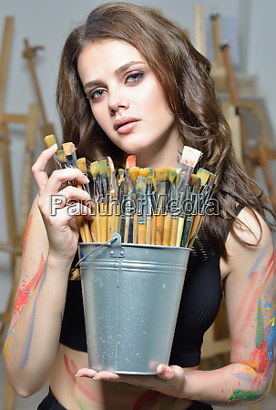 woman with brushes painting at art