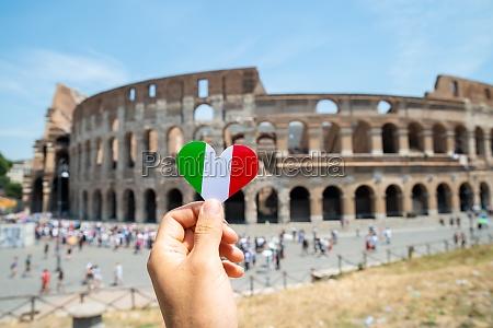 woman holding heart shaped italian flag