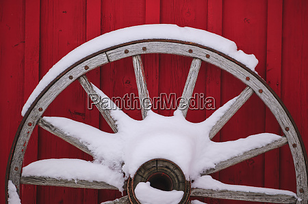 snow covered wagon wheels against red