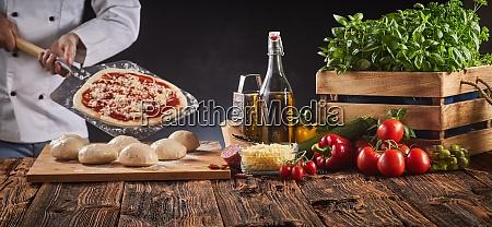 szef kuchni w pizzerii przygotowuje wloska