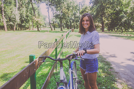 pretty young woman riding bicycle in