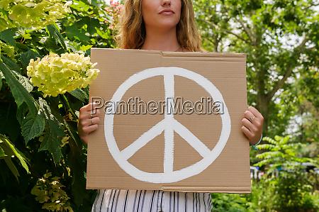 kobieta trzymajaca symbol pokoju przez drzewa