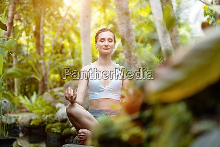kobieta robi joge w tropikalnej dzungli