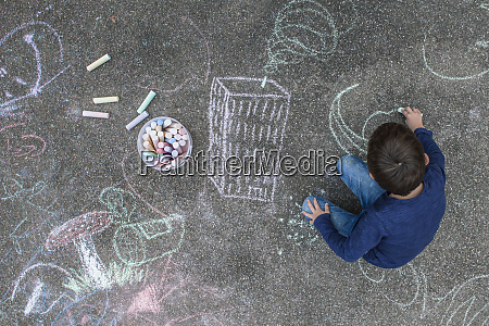 mlody chlopak rysunek na chodniku z