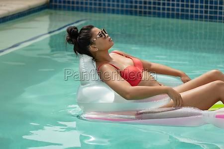 woman in bikini relaxing on inflatable