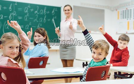 uczniowie w klasie podnoszacy rece aby