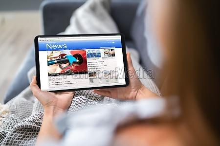 osoba ogladajaca wiadomosci na cyfrowym tablecie