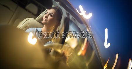Ladna mloda kobieta jazdy samochodem zaproszenie