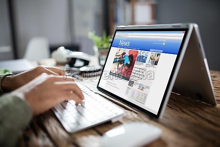 biznesmen czytanie wiadomosci na laptopie w