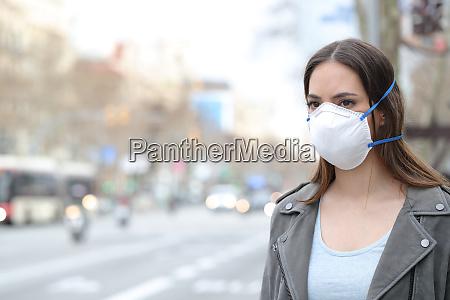 kobieta w masce ochronnej patrzac na