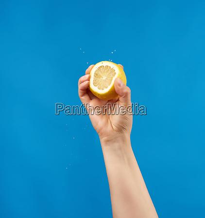 zenska reka trzyma pol zoltej cytryny