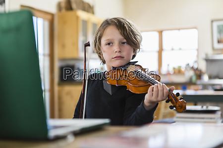 szescioletni chlopiec gra na skrzypcach majac