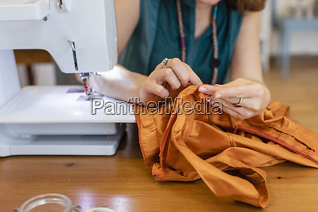 kobieta krawcowa szyjaca pomaranczowa tkanine w
