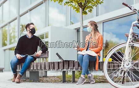 studenci na kampusie uniwersyteckim zachowujacy odleglosc