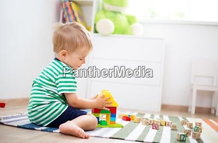 dwuletnie dziecko siedzace na podlodze z