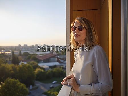 starsza kobieta stojaca na balkonie hotelu
