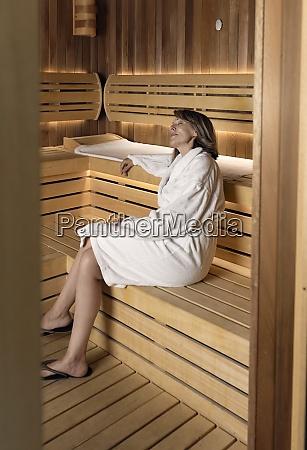 przemyslana kobieta ubrana w szlafrok siedzaca