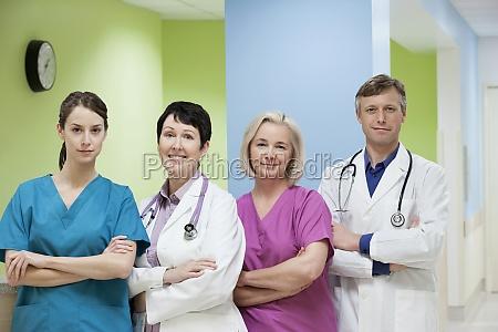 dwoch lekarzy stojacych z dwiema pielegniarkami