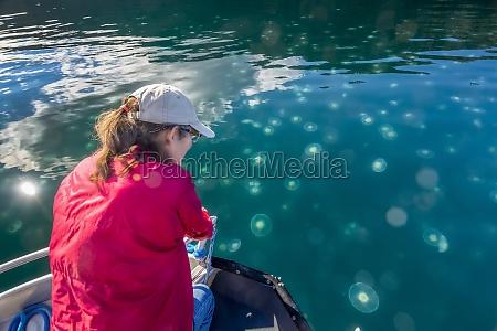 kobieta ogladajaca smack meduzy w wodach